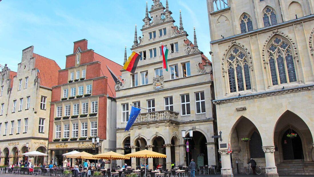 Am Prinzipalmarkt von Münster steht das beflaggte Stadtweinhaus von 1615, rechts daneben das Rathaus