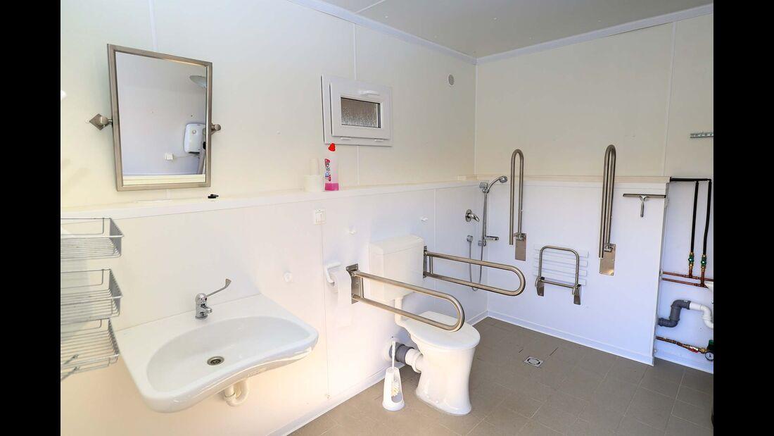 Behindertengergerechtes Badezimmer mit Waschbecken, Dusche und Toilette