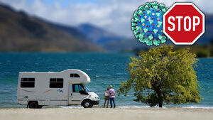 Couple outside camper looking at lake
