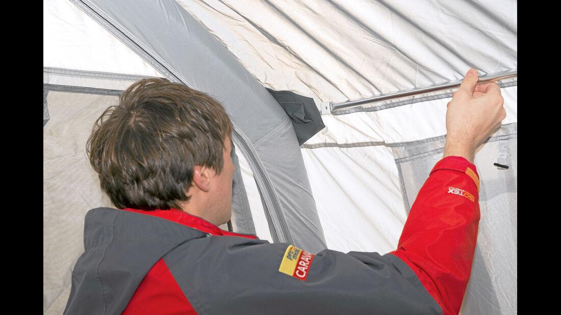 DWT stabilisiert das Zelt an der Dachkante mit einem Metallstab.