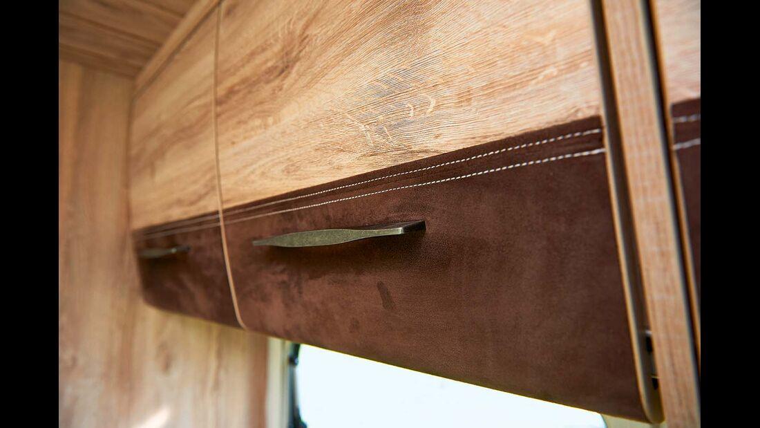 Das Chalet-Mobil bietet viele besondere Details – Schrankklappen mit Leder, gestickte Vorhangbordüren.