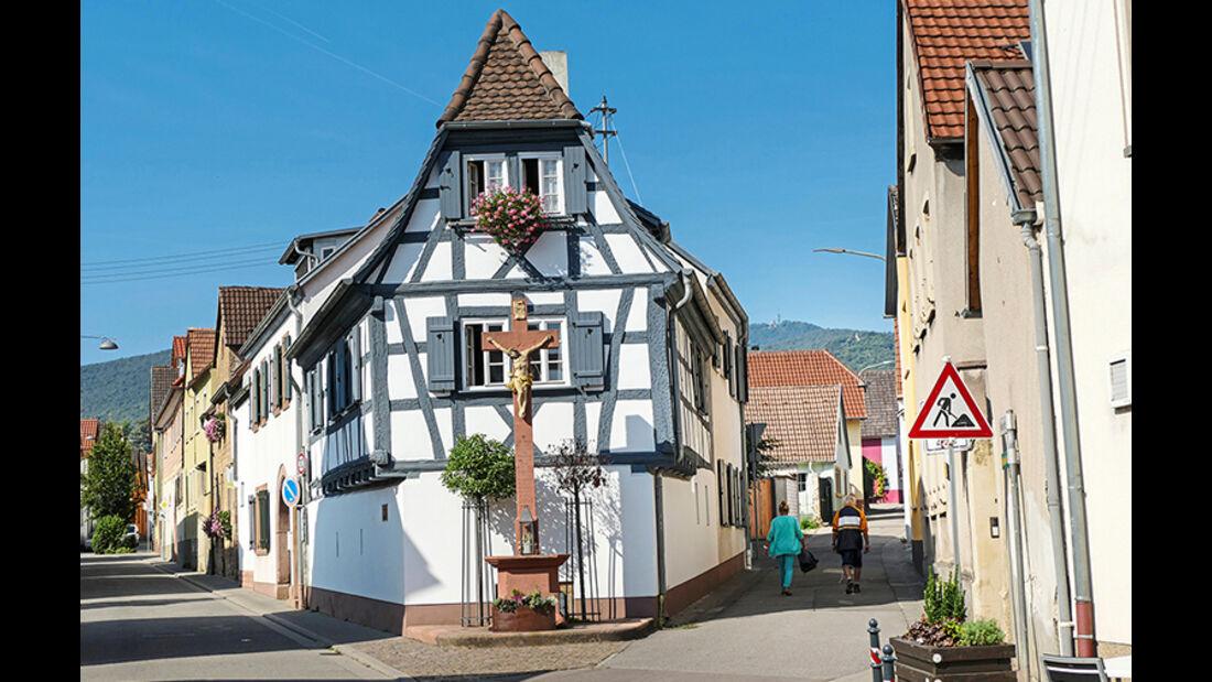 Das Kreuz vor dem Fachwerkhaus ist das Wahrzeichen von Maikammer, am Fuß der Kalmit, des höchsten Bergs im Pfälzerwald.