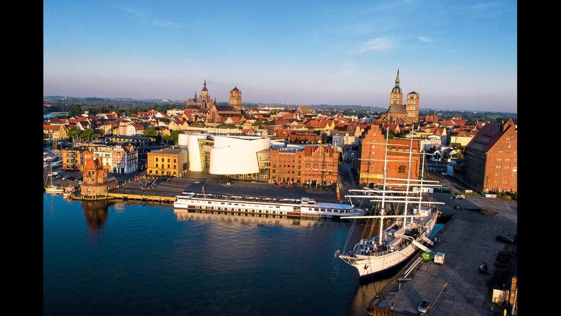 Das Ozeaneum in Stralsund mit seinen großen Aquarien leuchtet futuristisch zwischen den Backsteinbauten.