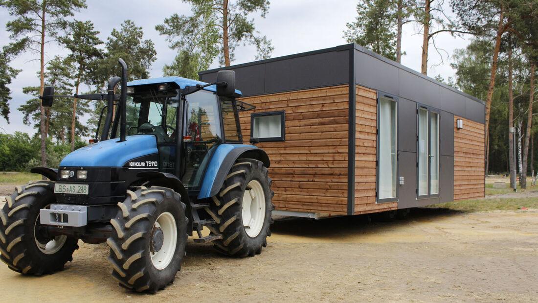 Der Aufbau des Mobile Home Parks auf dem Tropical Islands Gelände ist gestartet. Die ersten Häuser werden mit dem Traktor an ihren endgültigen Platz auf dem Campingplatz gebracht.