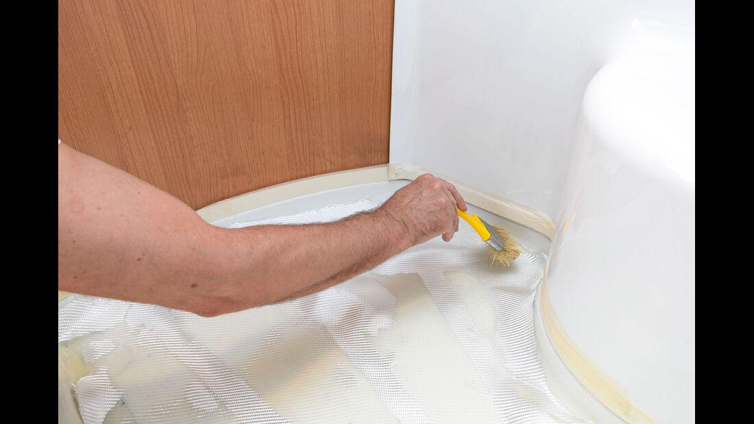 Der Modellbauer drueckt jede der insgesamt vier Glasfaserschichten luftblasenfrei fest.