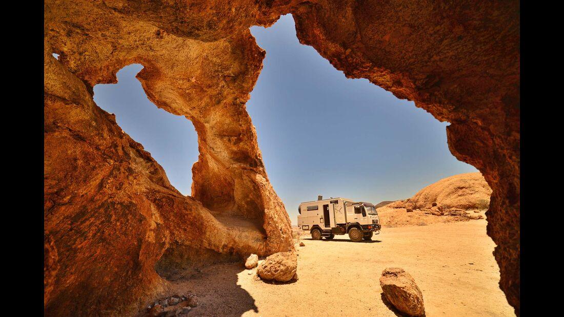 Der Stein des Rock Arch in Namibia leuchtet in der Abendsonne blutrot.