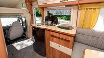 Die Küche ist ausgestattet mit Dreiflammenkocher, Edelstahlspüle, Apothekerschrank und 106-L-Kühlschrank.