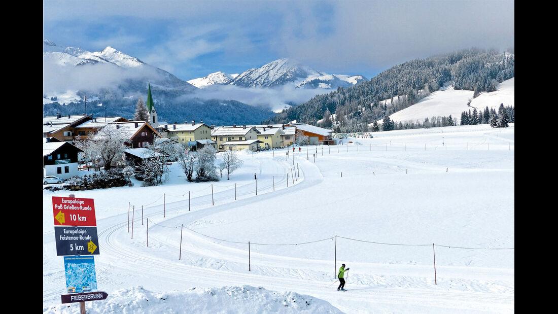 Die Loipe mitten durch das Dorf in Hochfilzen verlaeuft vor praechtigem Bergpanorama.
