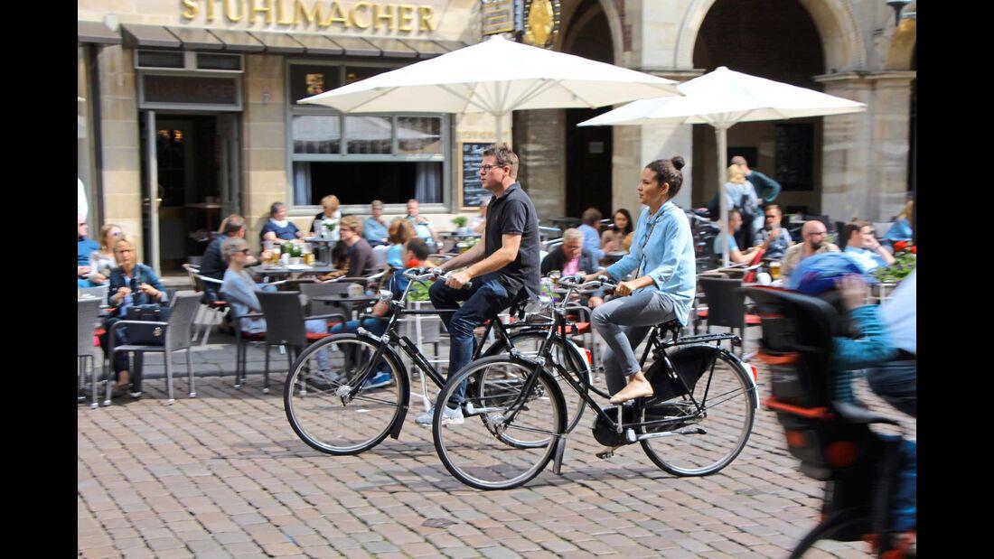 Die Münsteraner radeln gelassen am Weinhaus und am Rathaus vorbei.