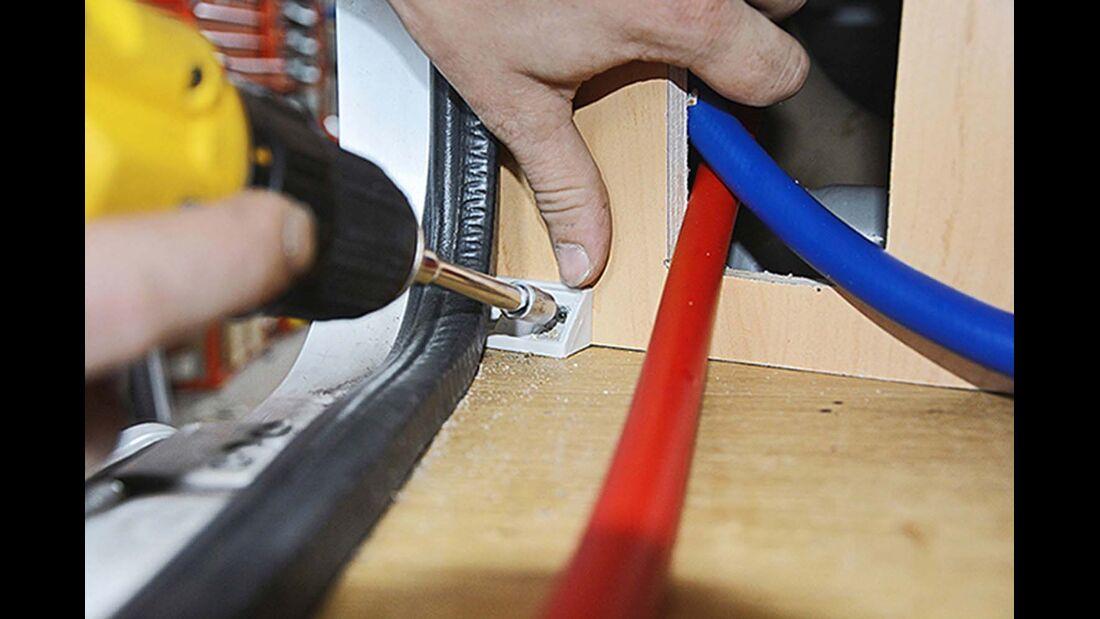 Die Schläuche durch die Aussparung der Montageplatte hindurchziehen und das Holz mit Winkelverbindern verschrauben.