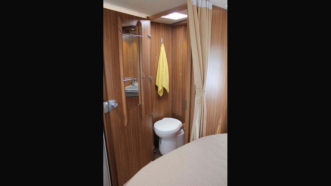 Die Toilette liegt auf der rechten Seite. Eine Tür kann den Gang zur Küche abschließen.