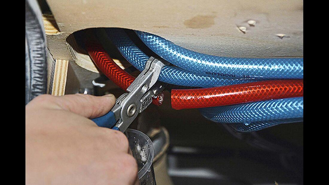 Die Warm- und Kaltwasserleitungen des Reisemobils werden gekappt und mit T-Stücken sowie zwei Schläuchen verbunden.
