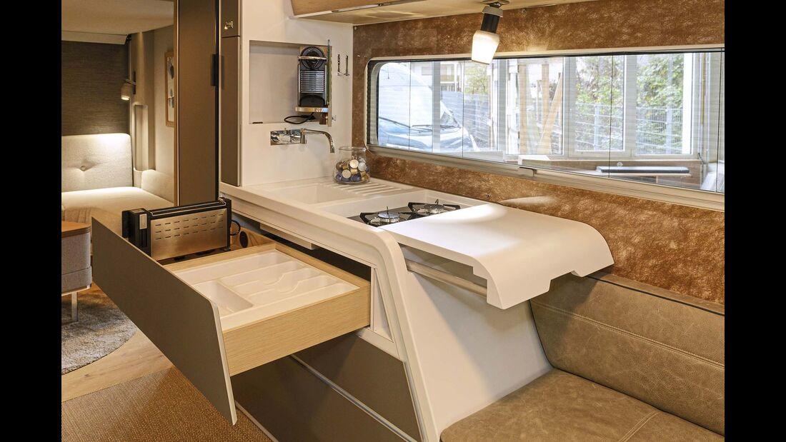 Die verschobene Abdeckung gibt zwei Kochflammen frei. Der Toaster ist in der Schublade, der Kaffeeautomat in der Seitenwand untergebracht.