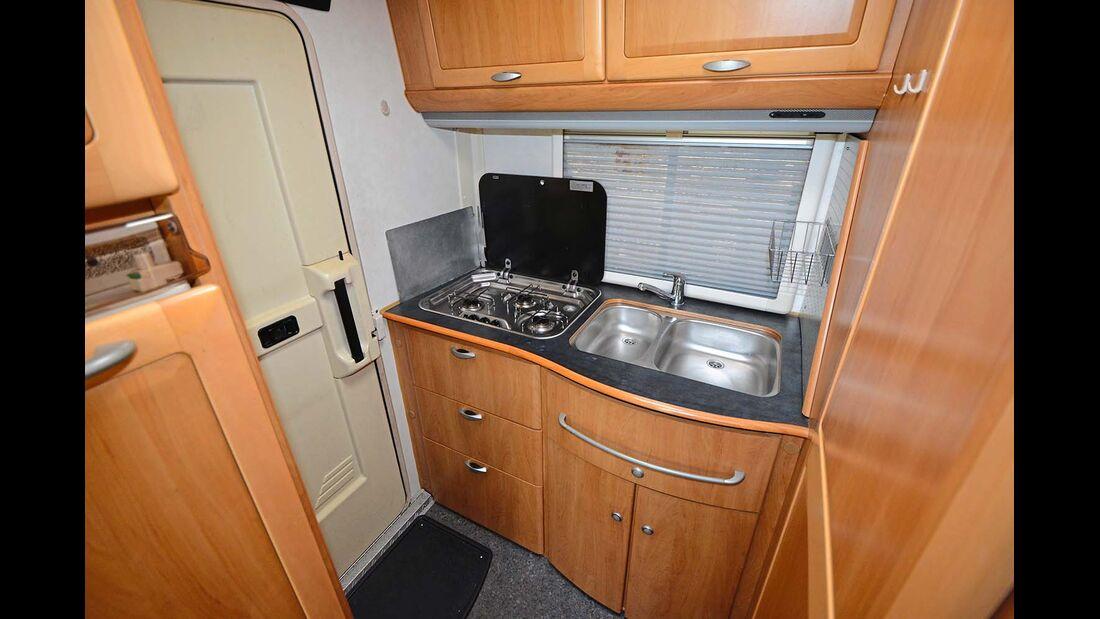 Durch den ausgelagerten Kühlschrank, hier links im Bild, hat die Heckküche reichlich Platz. Typisch für ältere Modelle ist die vergilbte Türverkleidung.