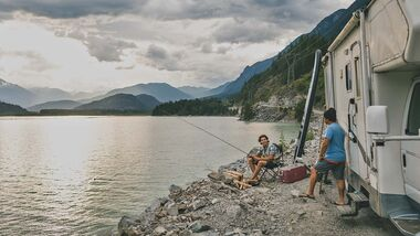 Father and son fishing by a lake