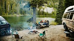 Friends sharing a meal while camping by lake
