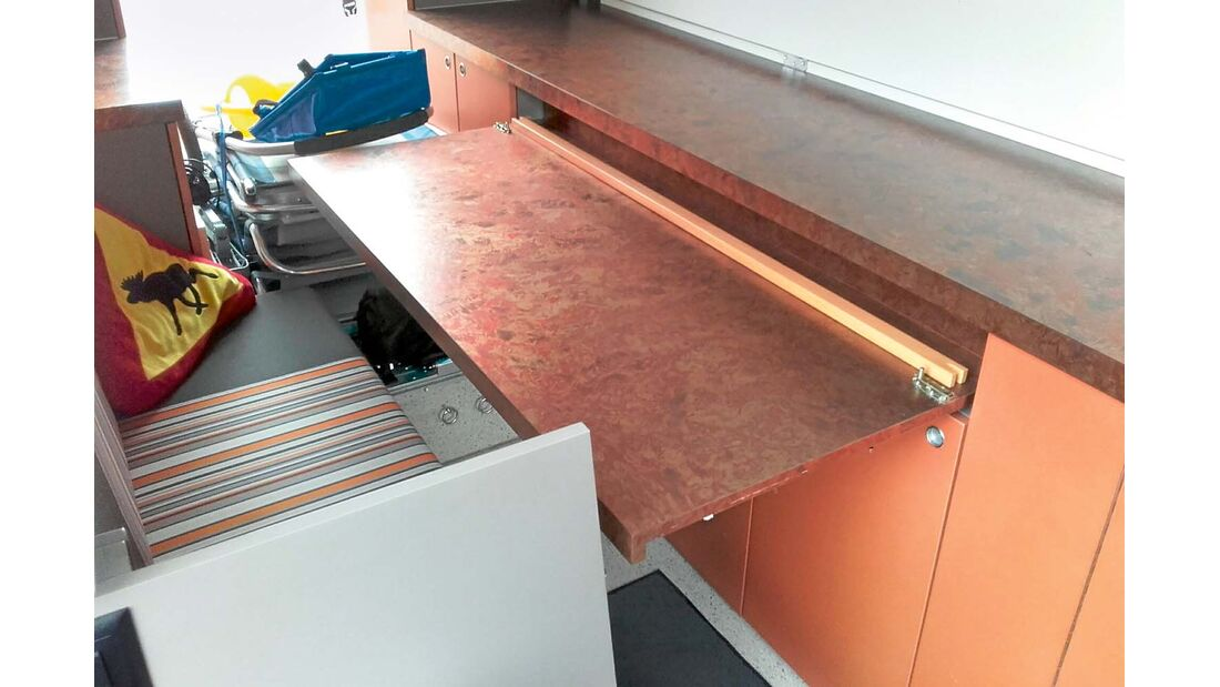 Gegenüber der Längsbank lässt sich die solide Tischplatte aus der langen Schrankzeile ziehen