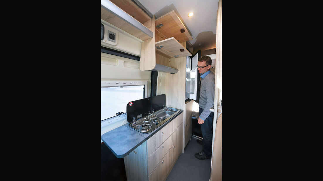Küche mit doppelstöckigen Hängeschränken und hohem Kühlschrank.