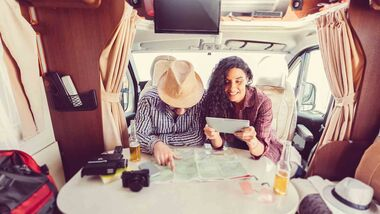 Mid adult couple planning road trip in campervan