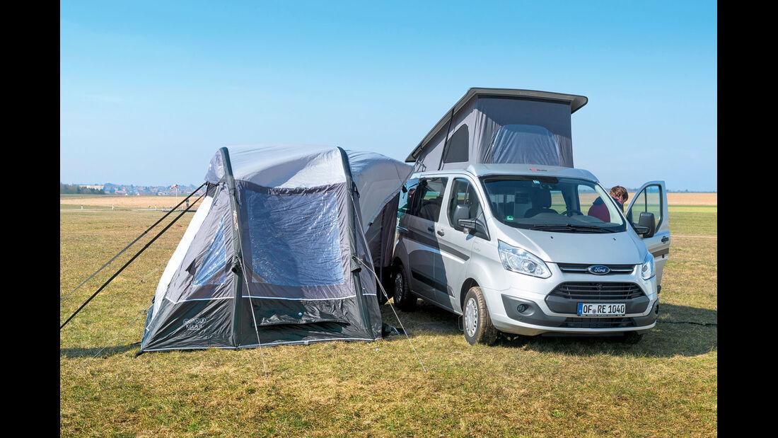 Mit Sturmleinen wird das Busvorzelt ueber das Dach des Campingbusses gespannt.