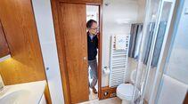 Solide Schiebetüren trennen das Bad mit seiner Keramik-Toilette zu beiden Seiten ab.