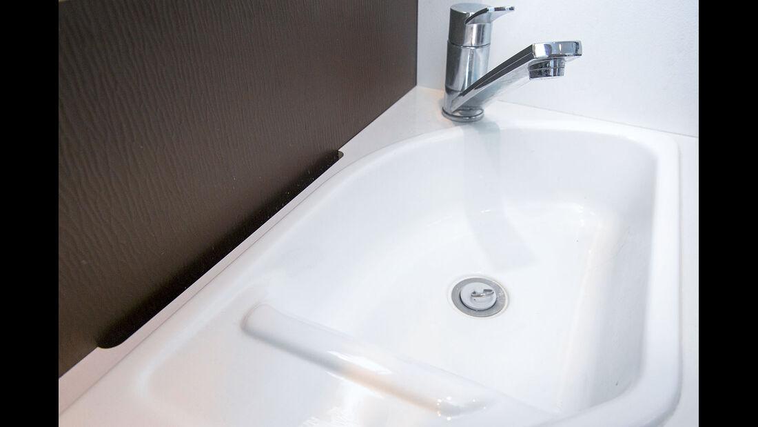 Wasser troepfelt in den Schlitz hinter dem Waschbecken.