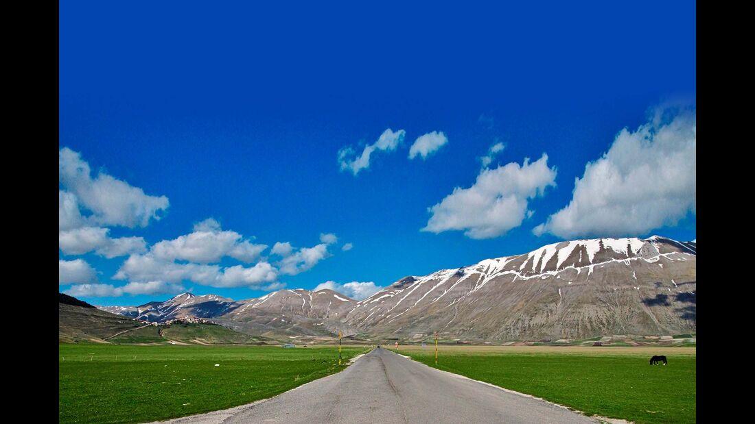 Weites Land: Wiesen, Schneegipfel, Hügel und Dörfer auf der Hochebene Altopiano di Castelluccio.
