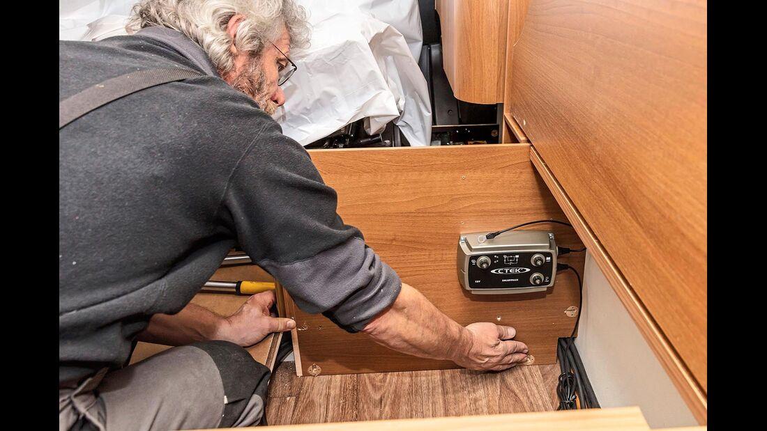 Wir platzieren das Ladesystem im Staufach unter der Seitensitzbank.