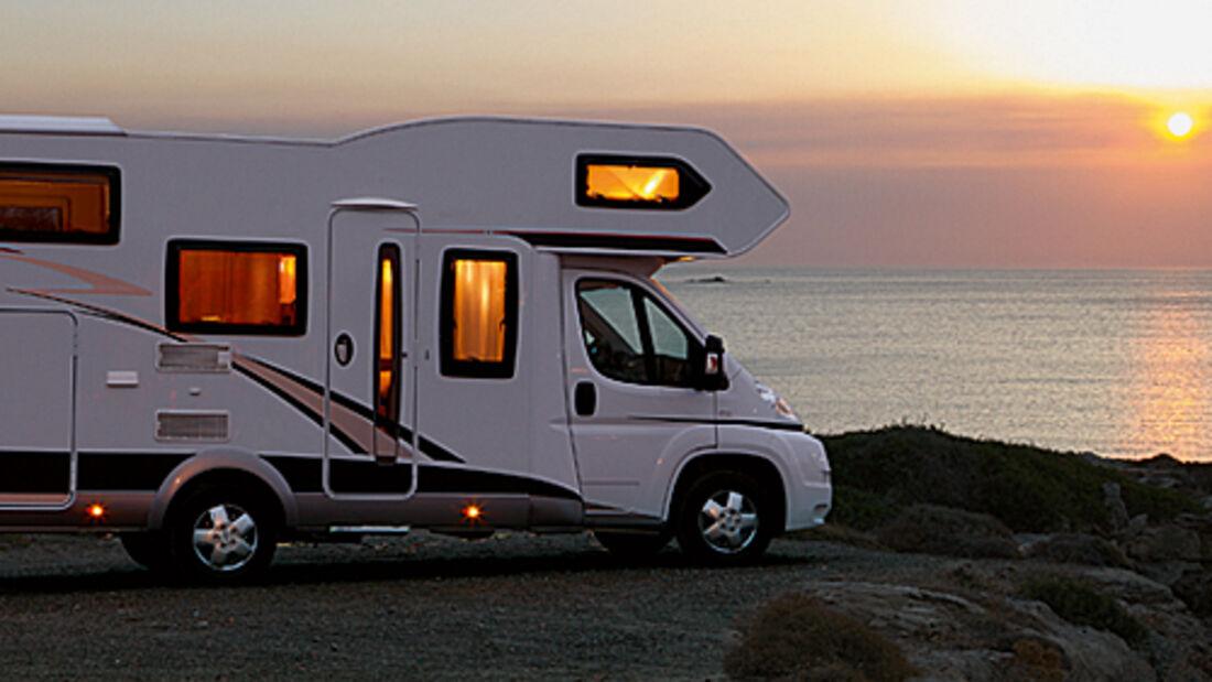 Wohnmobil steht bei Sonnenuntergang am Meer