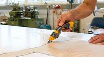 Zuerst schneidet der Modellbauer die Glasfasermatten zu.