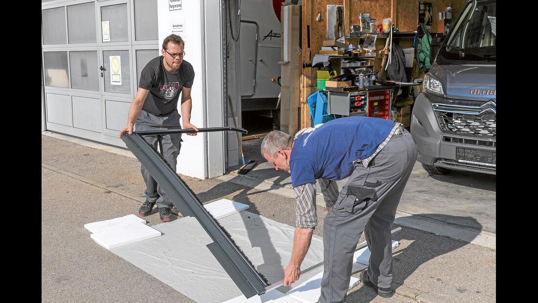 Zwei Personen passen den Rahmen im Kastenwagen ein.